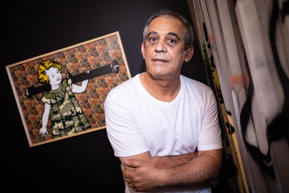 O grafiteiro Ozi posa diante de quadro com uma de suas personagens, 'Shirley', exposto na mostra retrospectiva de seus 35 anos de carreira na Chácara Lane, na Zona Central de São Paulo — Foto: Fábio Tito/G1