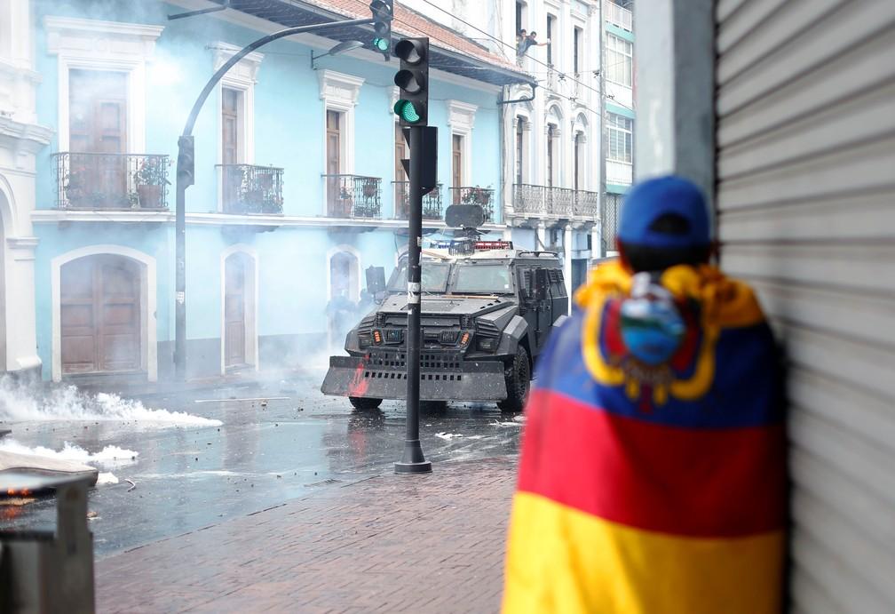 Manifestante enrolado em bandeira do Equador acompanha protestos em Quito contra aumento dos combustíveis — Foto: Daniel Tapia/Reuters