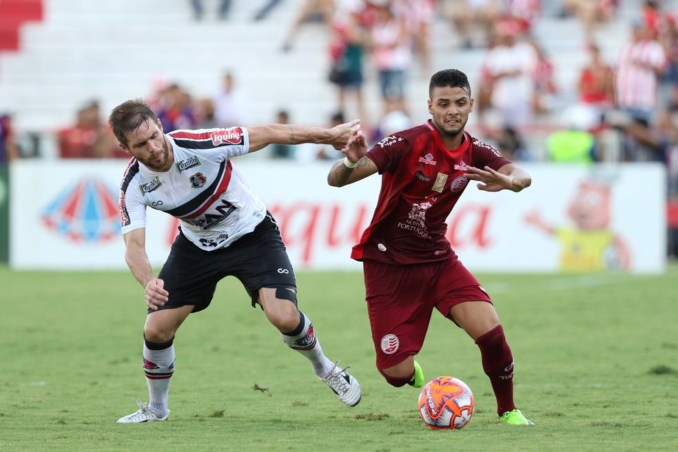 Diego Lorenzi e Odilávio disputam a bola no último clássico; nenhum dos dois vai estar em campo no sábado — Foto: Marlon Costa/ Pernambuco Press