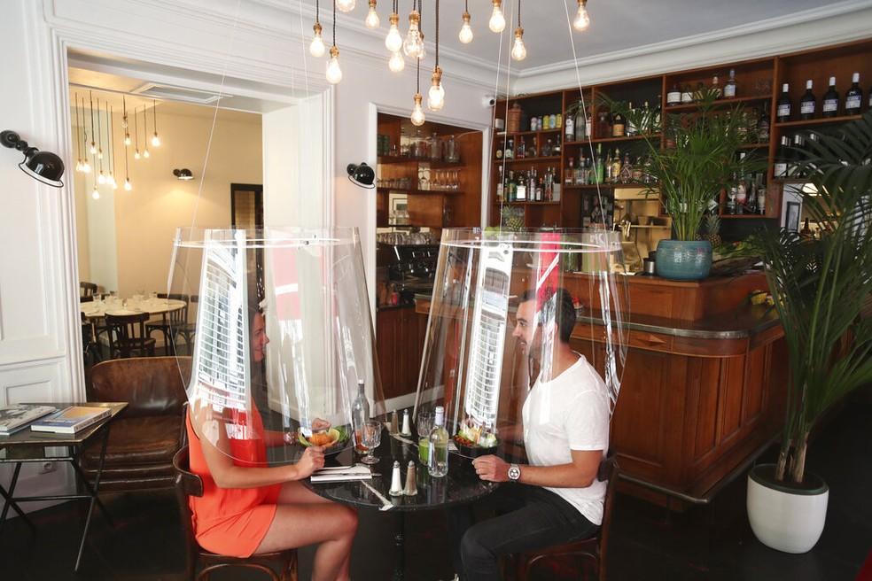 Casal coberto com a proteção de plástico — Foto: Thibault Camus/AP