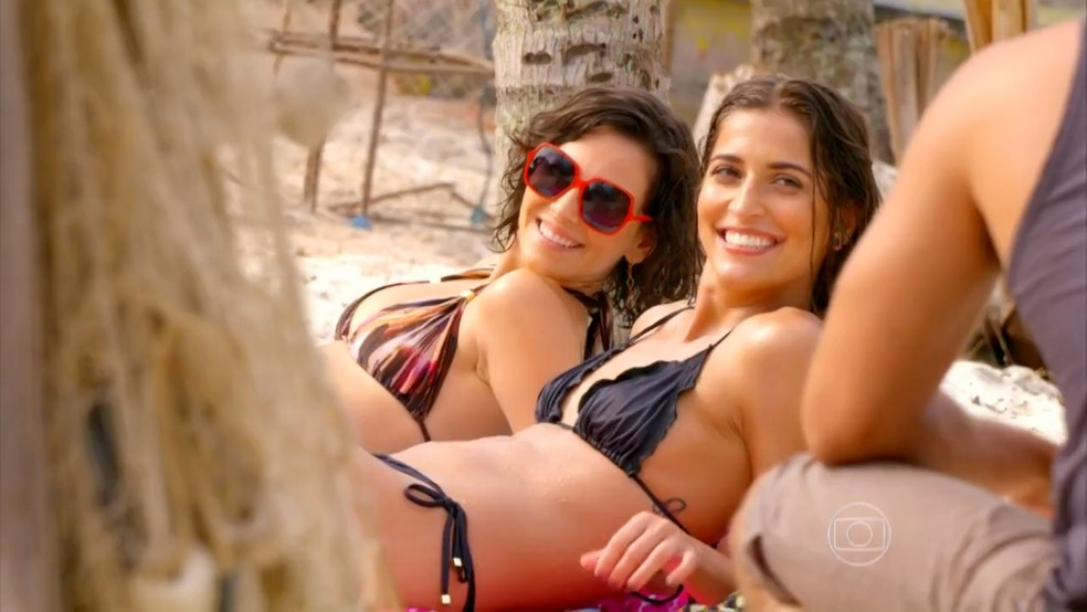 Mila (Tainá Müller) e Carol (Maria Joana) se interessam por Juliano (Bruno Gissoni) - 'Flor do Caribe' — Foto: Globo