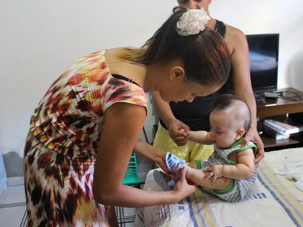 A jovem cuida do pequeno Lorenzo durante todo o dia (Foto: Hosana Morais/G1)