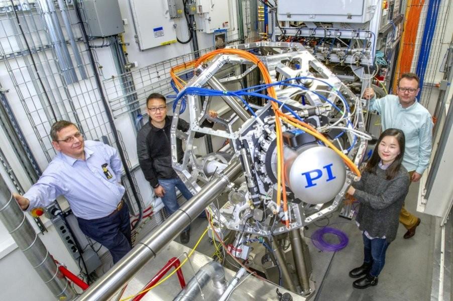 O pesquisador Haotian Wang (de jaqueta preta) com aparelho cuja meta é converter o CO2 em combustíveis utilizados no meio industrial (Foto: Divulgação/Brookhaven National Laboratory)