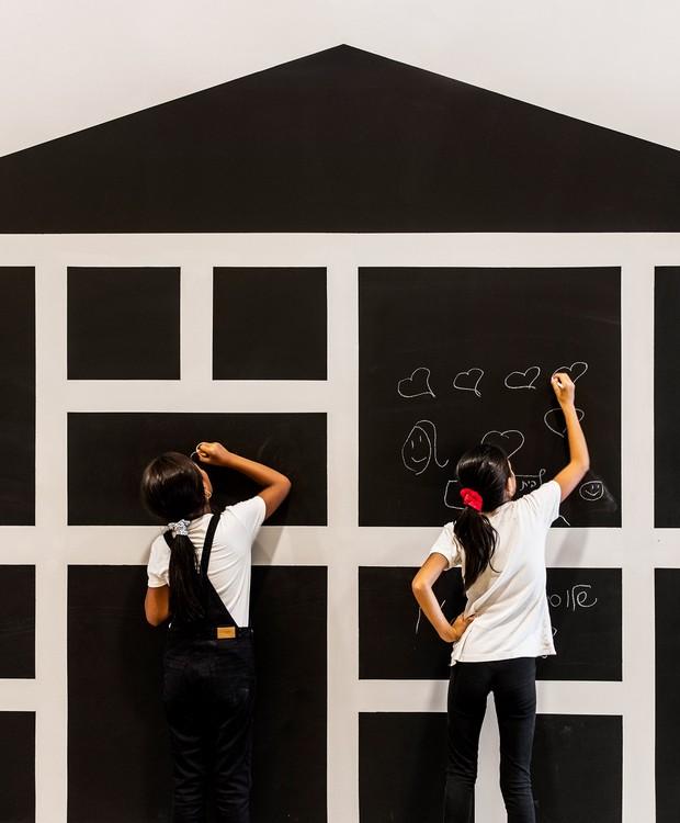 Em formato de casa, uma parede recebeu quadrados pintados em tinta de lousa. Ali, as crianças tem espaços individuais para desenhar (Foto:  Itay Benit/ Dezeen/ Reprodução)