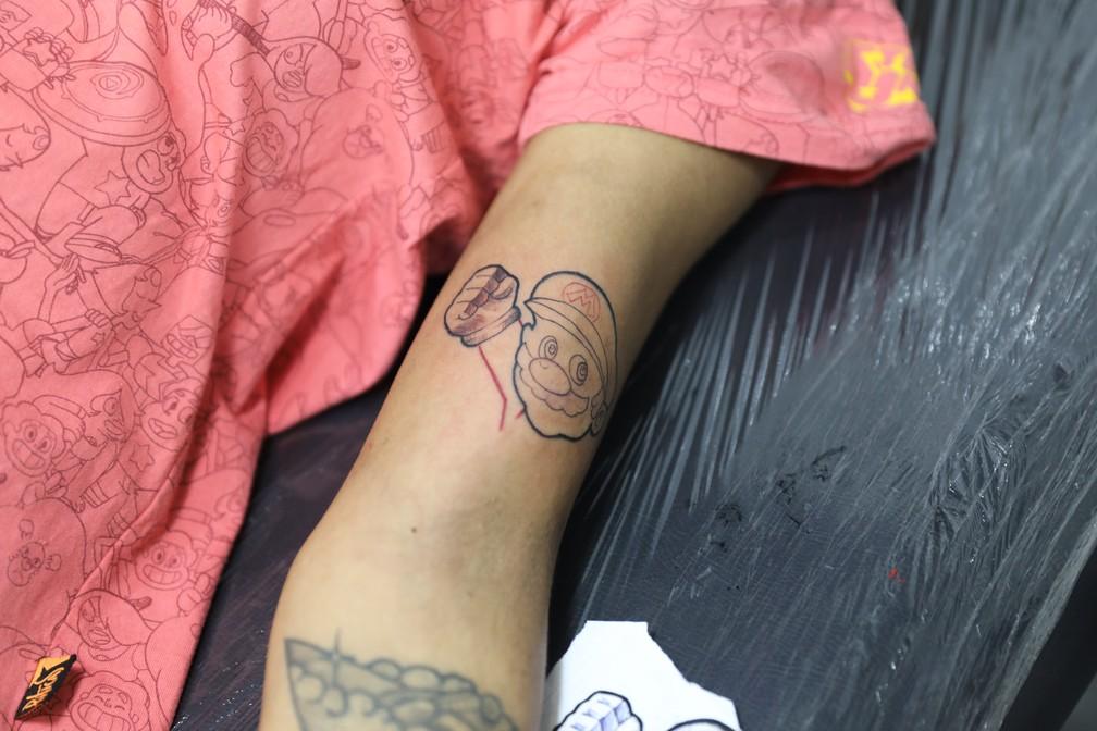James Jim tatua um Mario na analista de risco Juscilene Ferreira dos Reis, de 28 anos, na CCXP 2018 — Foto: Fábio Tito/G1