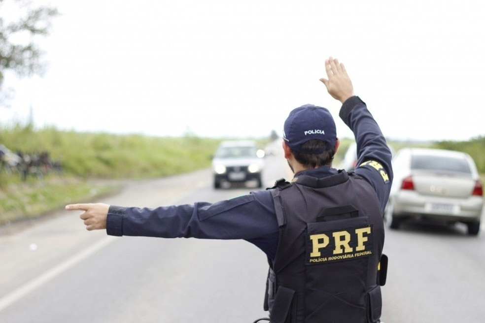 Agente da Polícia Rodoviária sinaliza para motorista durante abordagem — Foto: PRF/Divulgação