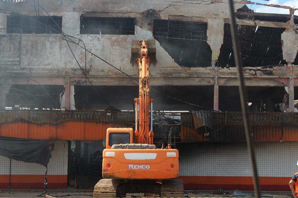 Retroescavadeira inicia demolição da fachada de loja de autopeças que pegou fogo, em Porto Velho. — Foto: Pedro Bentes/G1