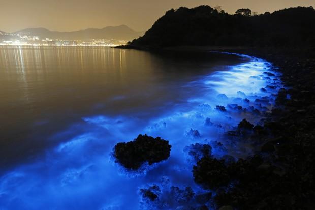 Foto feita com longa exposição mosra o brilho da Noctiluca scintillans na costa de Hong Kong (Foto: AP Photo/Kin Cheung)