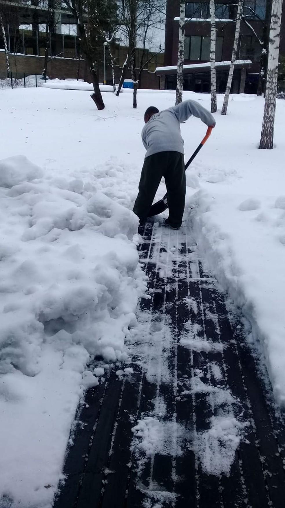 Robson retira excesso de neve da porta da casa de Fernando — Foto: Arquivo Pessoal