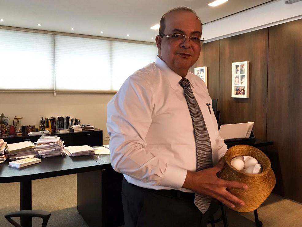 O governador eleito do DF, Ibaneis Rocha, segura cesto de ovos que adorna sala do escritório do advogado  — Foto: Letícia Carvalho/G1