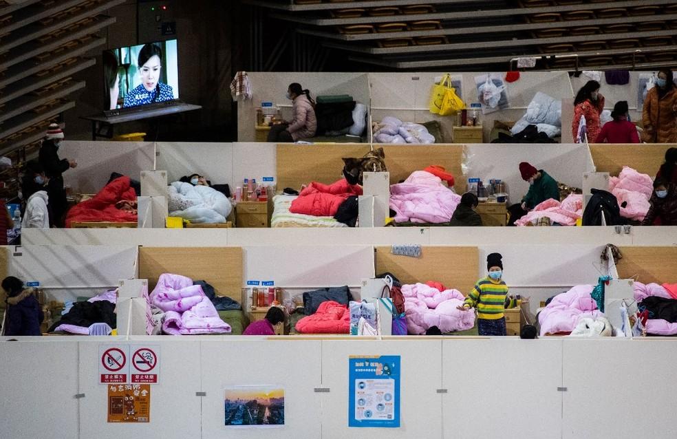 Imagem do dia 18 de fevereiro mostra pacientes com sintomas leves de Covid-19, a doença do novo coronavírus, em alojamento temporário do Hospital Fengcai, instalado em um estádio esportivo de Wuhan, na China. — Foto: STR/AFP