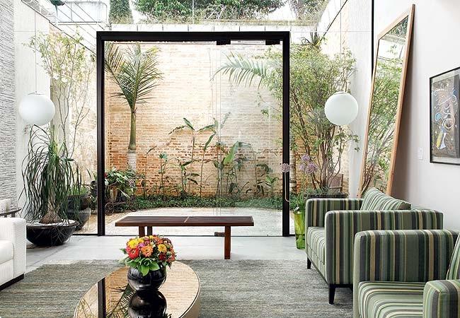 A esquadria é mínima para aproximar ainda mais a sala do jardim, que tem palmeiras-garrafa, helicônias e um imponente muro de tijolos de demolição. Os arranjos de zínia e de flor-de-alho foram feitos pela paisagista (Foto: Casa e Jardim)