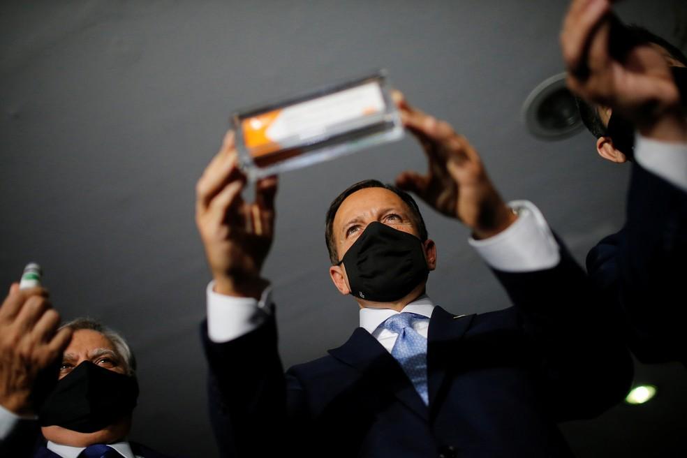 O governador de São Paulo, João Dória, exibe a vacina Coronavac. — Foto: Adriano Machado/Reuters