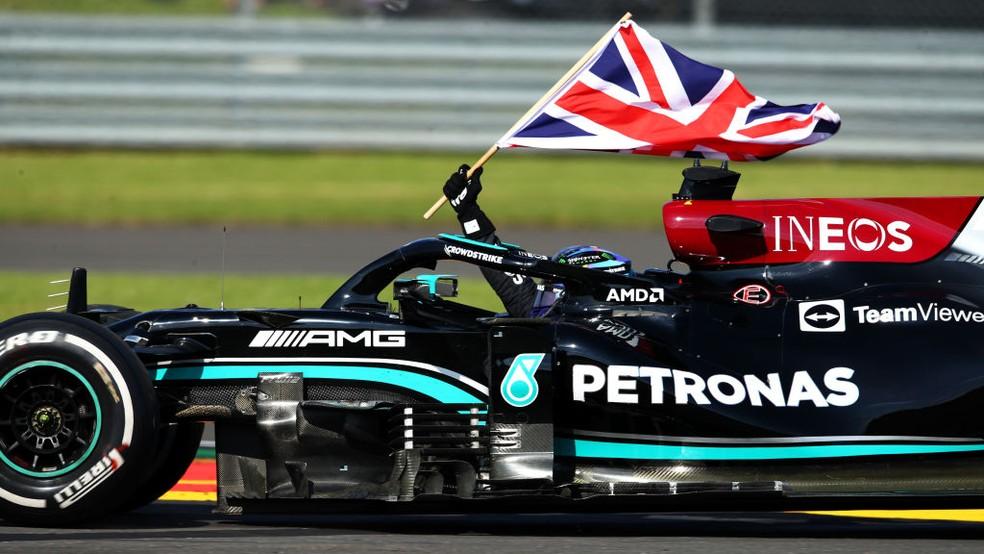 Lewis Hamilton comemora oitava vitória no Circuito de Silverstone com bandeira britânica — Foto:  Joe Portlock - Formula 1/Formula 1 via Getty Images