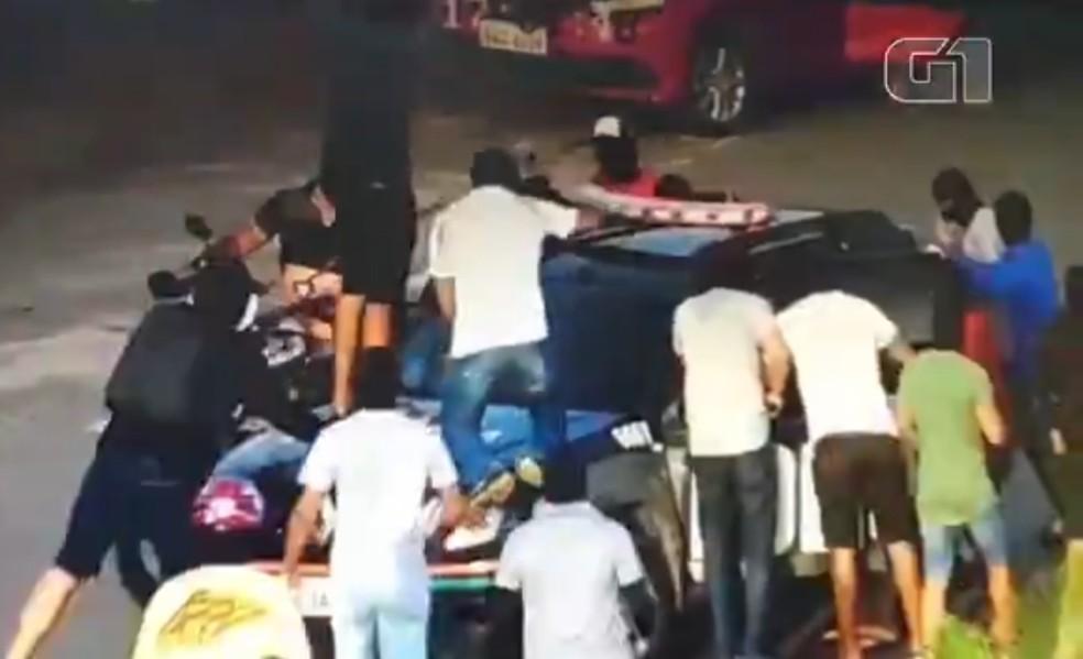 Bando de encapuzados cerca e toma veículo oficial de policiais em Fortaleza — Foto: Reprodução