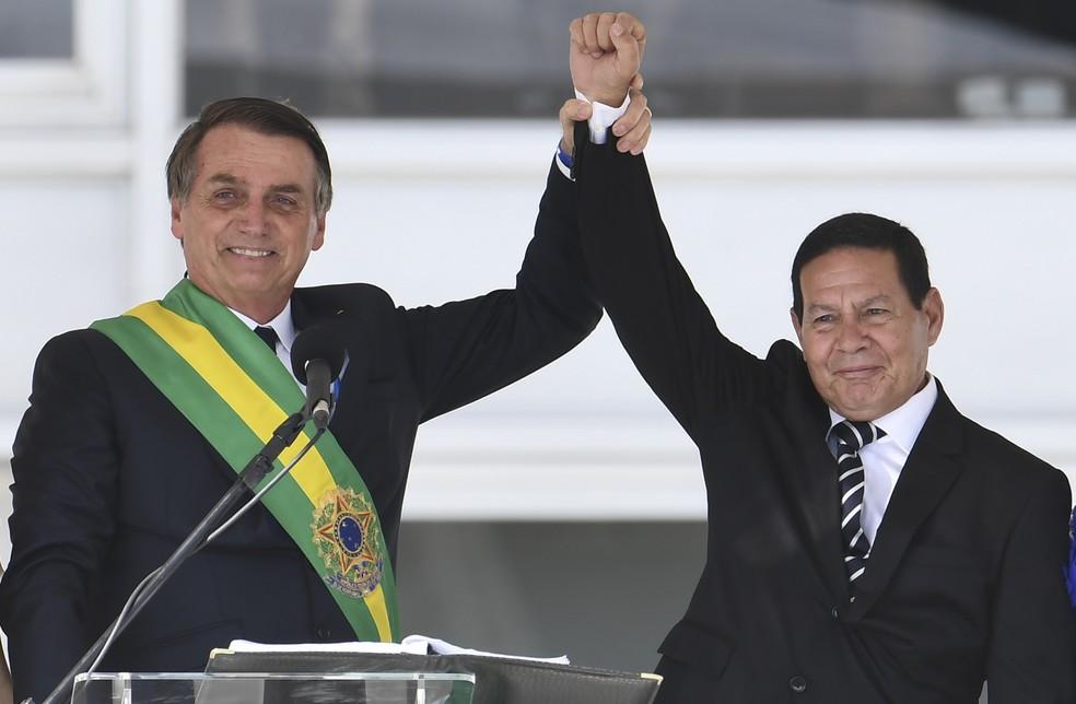 O vice-presidente do Brasil, general Hamilton Mourão, ao lado do presidente Jair Bolsonaro — Foto: Evaristo Sá/AFP