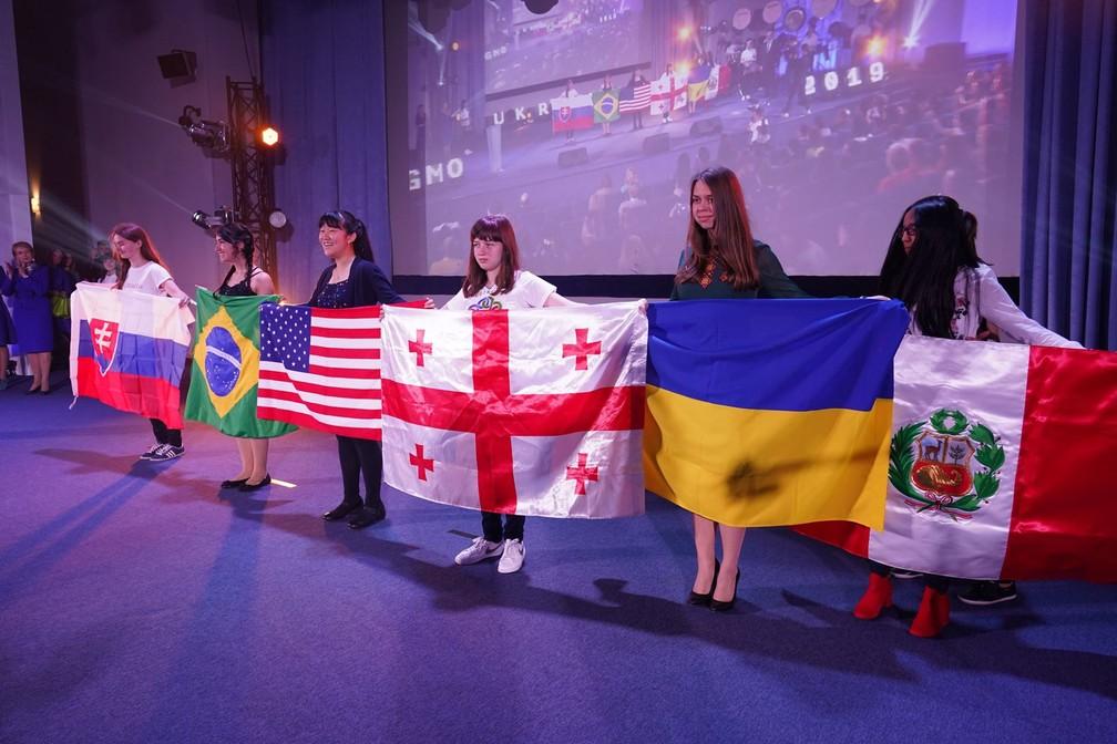 Com a bandeira brasileira, Mariana Groff sobe ao palco ao lado das demais medalhistas de ouro da olimpíada de matemática — Foto: Divulgação/EGMO