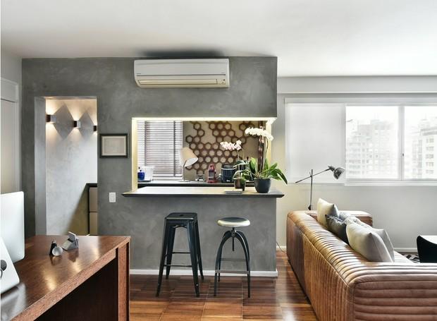 INTEGRAÇÃO | A arquiteta decidiu fazer um rasgo na parede para criar uma bancada, transformando o espaço em um bar. Banquetas da Thonart - Isto é Brasil. Luminária ao lado do sofá da Bertolucci (Foto: Sidney Doll/Divulgação)