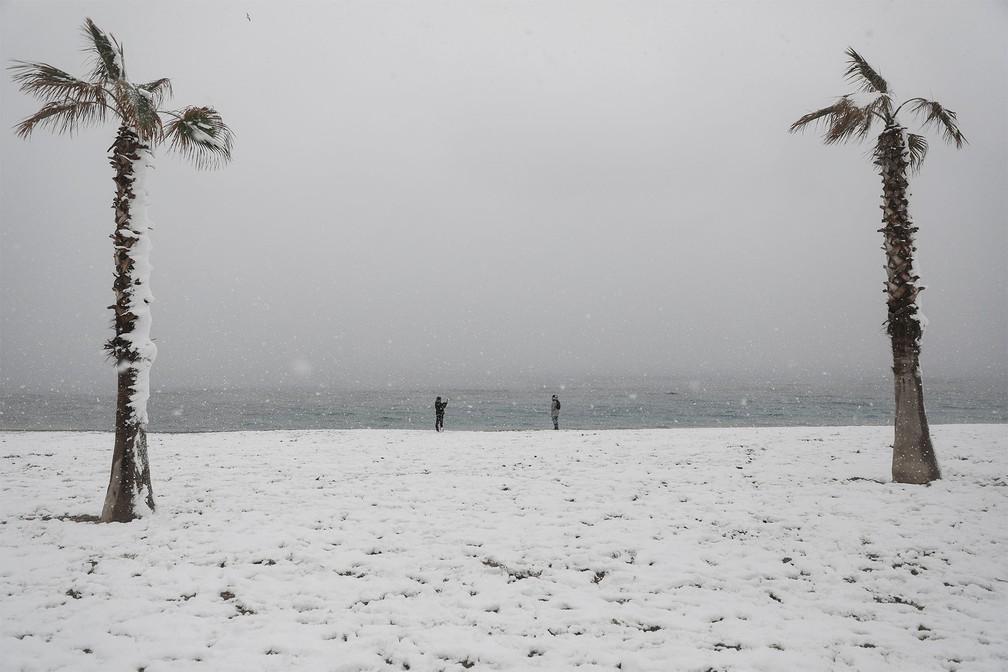 Pessoas tiram fotos em praia coberta de neve em Glyfada, subúrbio de Atenas, na Grécia — Foto: Stelios Misinas/Reuters