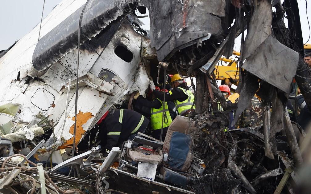 Funcionários trabalham entre os destroços do avião da US-Bangla Airlines que caiu no aeroporto de Katmandu, no Nepal, na segunda-feira (12) (Foto: Prakash Mathema/AFP)