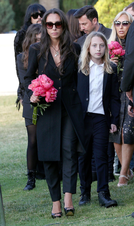O jovem Christopher Nicholas, filho de Chris Cornell (1964-2017), no funeral do pai na companhia de sua mãe (Foto: Getty Images)