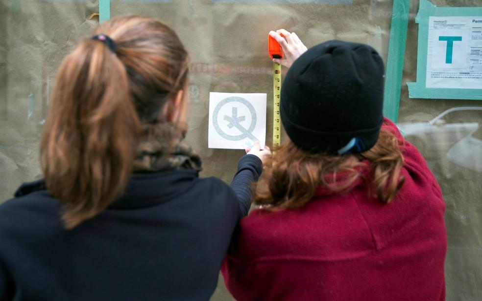 Funcionárias se preparam para colocar logotipo em uma vitrine coberta da Quebec Cannabis Society (SQDC), um dia antes de o Canadá legalizar a maconha recreativa — Foto: Reuters/Christinne Muschi
