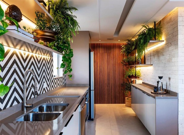 Painéis em ripas de cumaru camuflam as portas da sauna e banheiro ao fundo. Destaque para o projeto luminotécnico do próprio escritório. (Foto: Raul Fonseca/Divulgação)