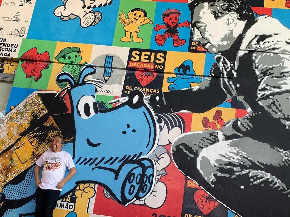 Mauricio de Sousa posa diante de painel em sua homenagem na Bienal — Foto: Fernanda Rouvenat/G1