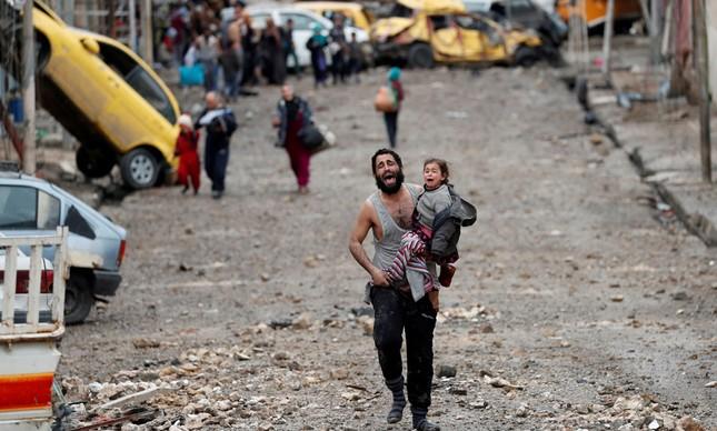 Pai corre com a filha no colo em Mosul, no Iraque