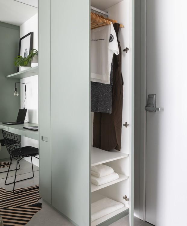 O armário com cabideiro fica junto à entrada do apartamento. Em sua lateral, há um pequeno espaço separado para guardar itens como tábua de passar e vassouras, que dão conta da rotina de limpeza (Foto: Evelyn Müller/Divulgação )