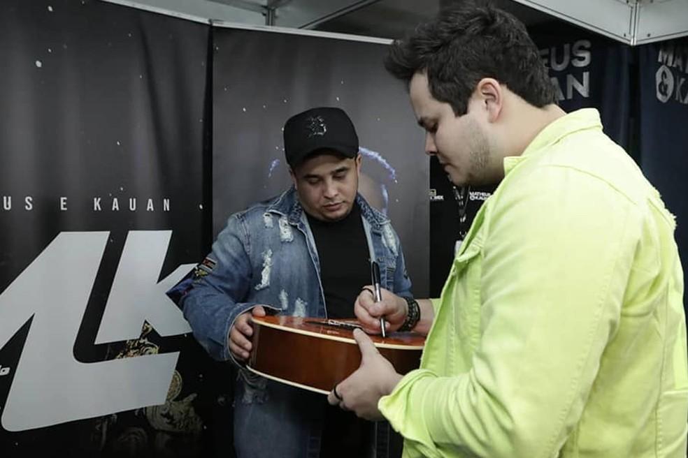 Matheus & Kauan abraçaram a causa social do VillaMix Uberaba e assinaram o violão, que será leiloado em prol do Hospital Hélio Angotti — Foto: ANDRÉ SANTOS