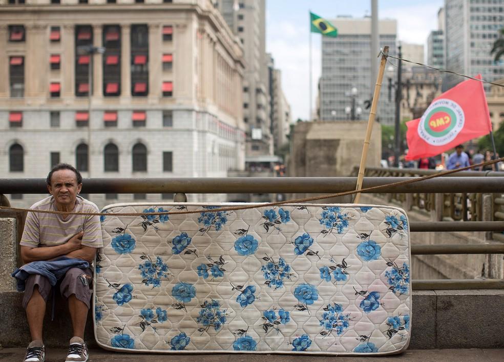 Um ativista do Movimento dos Trabalhadores Sem Teto se senta ao lado de seu colchão durante um protesto contra os cortes orçamentários do governo em programas de habitação de baixa renda em São Paulo — Foto:  Andre Penner/AP