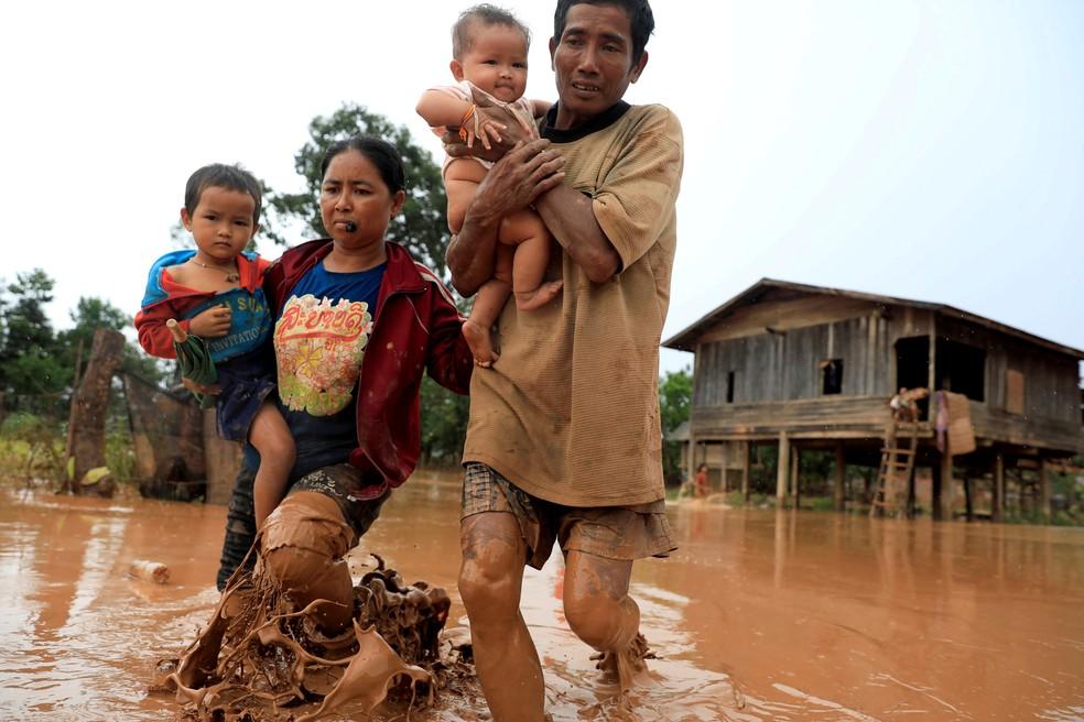 Família deixa a sua casa em meio a enchente na província de Attapeu, no Laos, após rompimento de represa, em imagem de arquivo (Foto: Soe Zeya Tun /Reuters)
