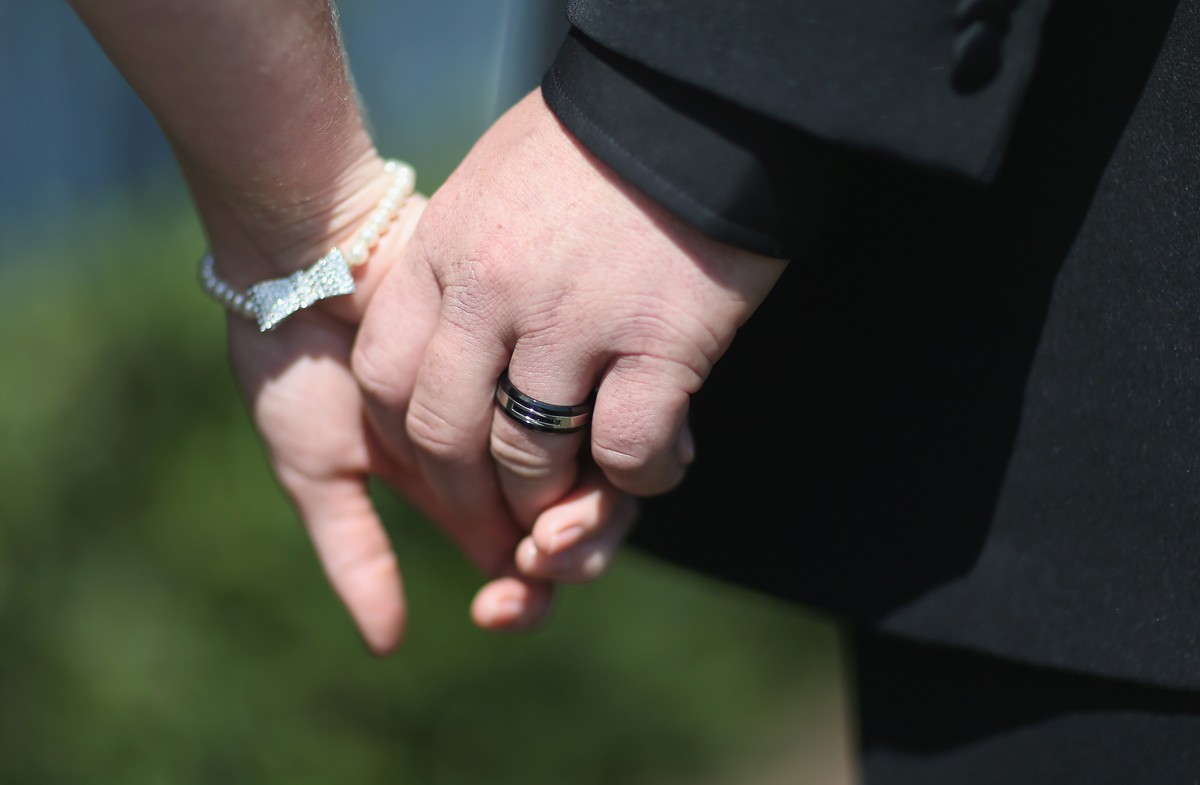 WEST PALM BEACH, FL - FEBRUARY 14:  A couple holds hands as they are wed during a group Valentine's day wedding at the National Croquet Center on February 14, 2014 in West Palm Beach, Florida. The group wedding ceremony is put on by the Palm Beach Country (Foto: Getty Images)