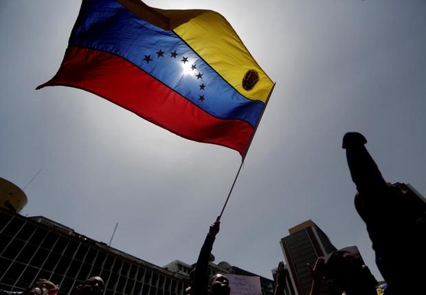 Manifestante empunha bandeira da Venezuela durante marcha contra o governo de Nicolás Maduro em Caracas (Foto: Marco Bello/Reuters)
