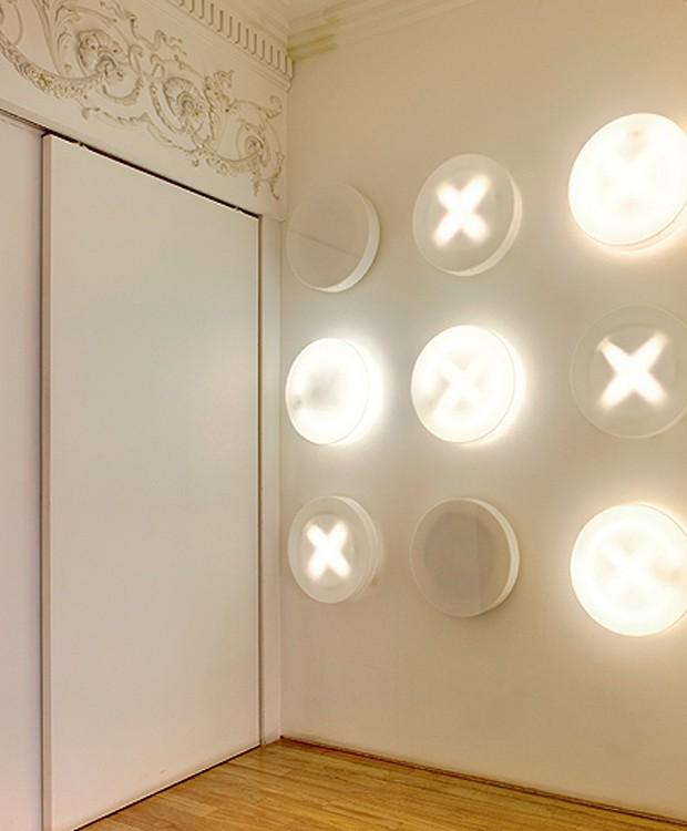 Enquanto os convidados esperam no hall de entrada da arquiteta Valéria Blay, podem se divertir com o jogo da velha na parede do ambiente de 7,50 m². As luminárias escondem lâmpadas que acendem e apagam ao toque de imperceptíveis interruptores (Foto: Edu Castello/Casa e Jardim)