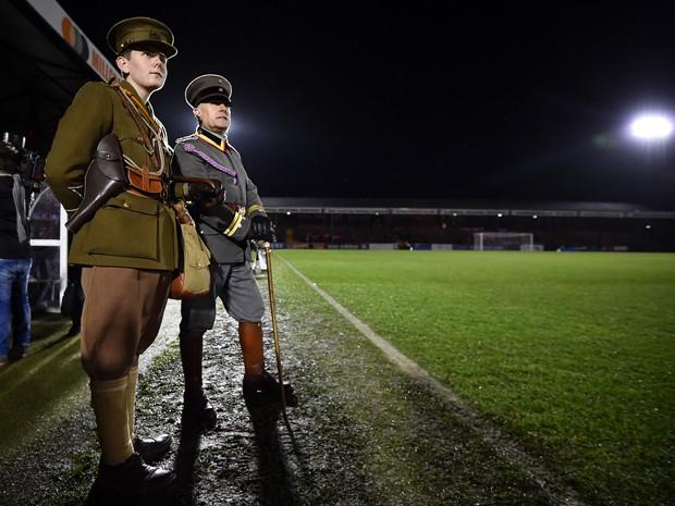 Dois homens com réplicas de uniformes militares da I Guerra Mundial assistem ao jogo que recria uma partida disputada no Natal de 1914, em Aldershot, na quarta (17) (Foto: AFP Photo/Ben Stansall)