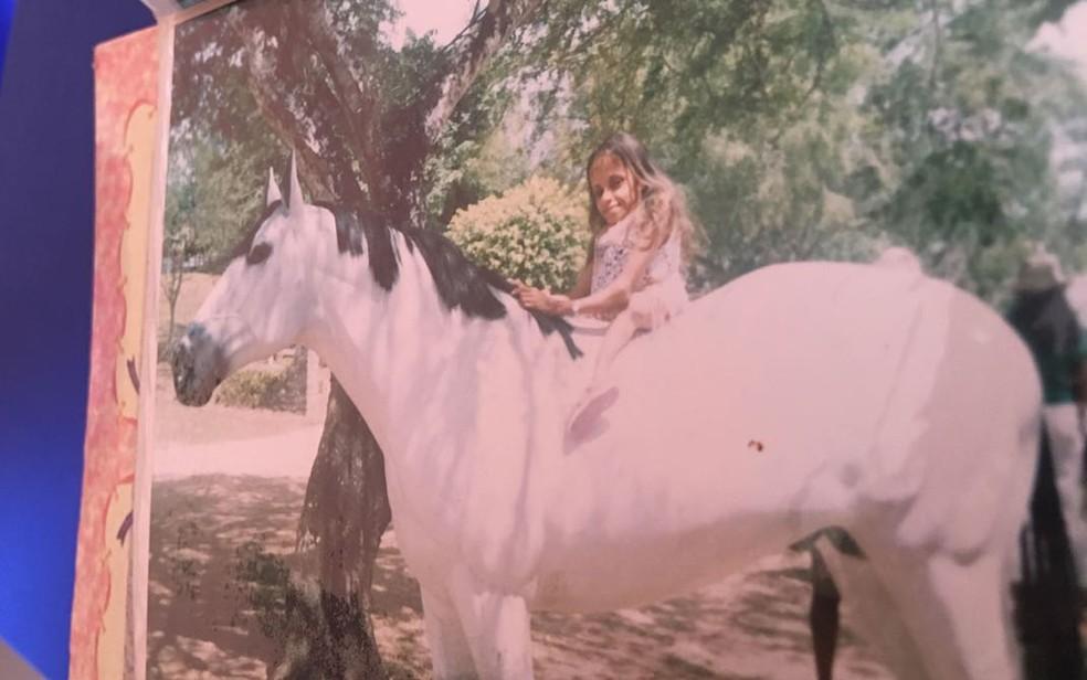 Fotografia em álbum mostra Glady montada em cavalo durante viagem (Foto: Juliana Almirante/ G1)