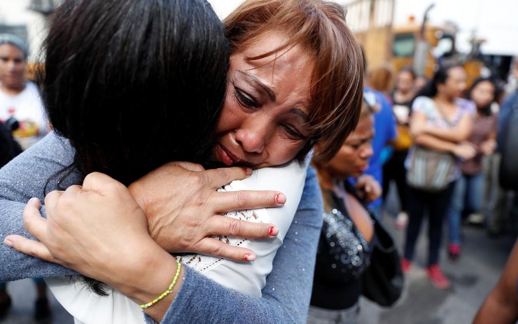 Parentes de prisioneiros choram do lado de fora do centro de detenção Helicoide, em Caracas, após conflitos no local, na quarta-feira (16) (Foto: Reuters/Carlos Garcia Rawlins)