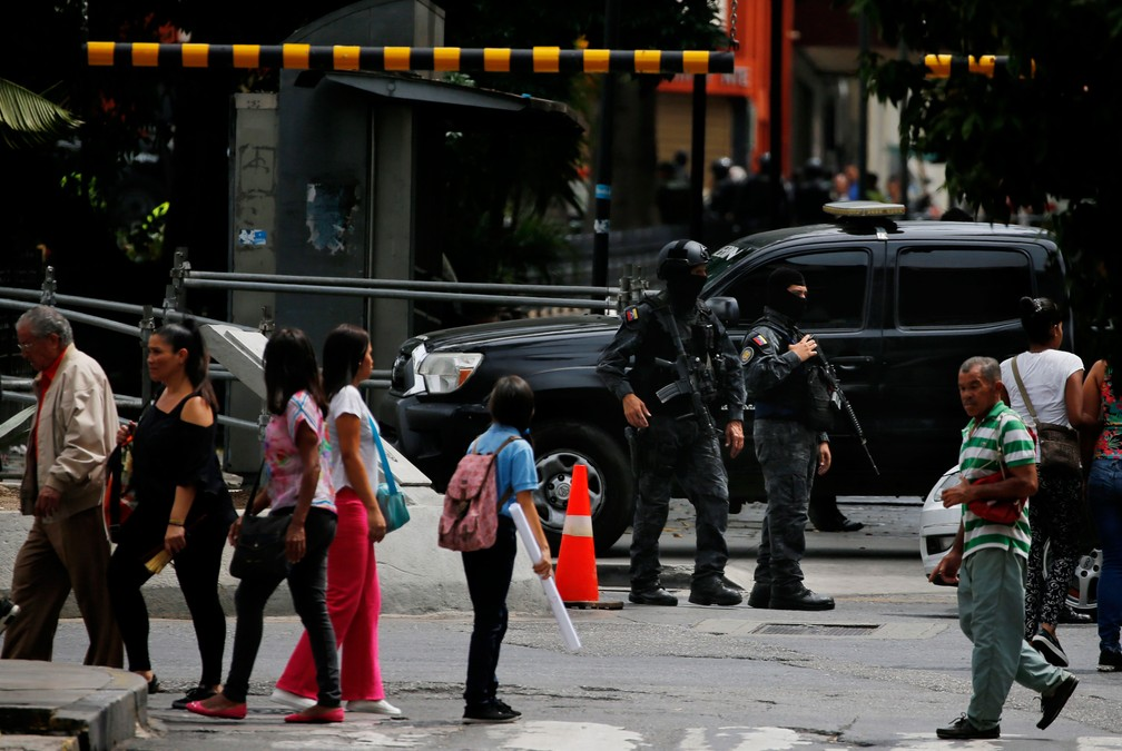Agentes mascarados da agência de inteligência da polícia venezuelana montam guarda na entrada da Assembleia Nacional da Venezuela nesta terça-feira (14) — Foto:  Fernando Llano/ AP