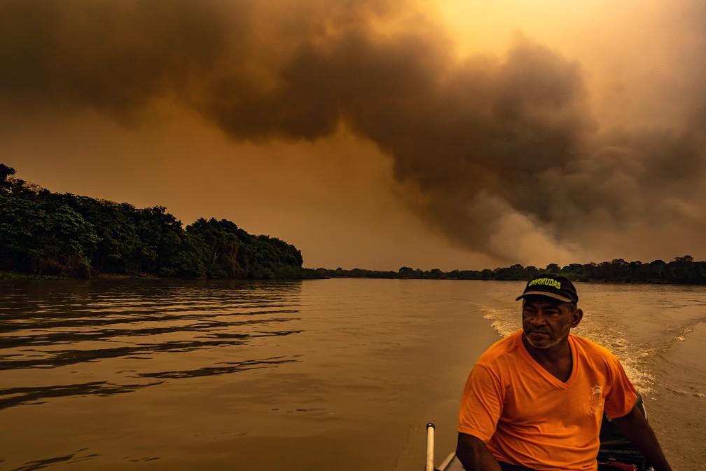 Registro de pantaneiro no barco e com incêndios ao fundo foram compartilhados por diversas vezes nas redes sociais — Foto: BRUNA OBADOWSKI/A LENTE