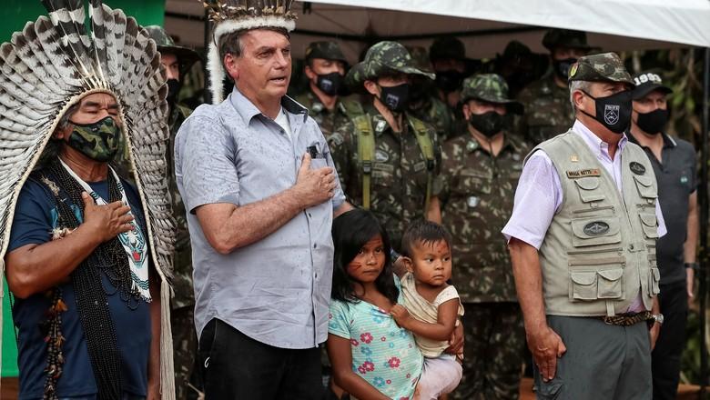 Presidente Jair Bolsonaro ouve o hino nacional em visita a terras indígenas, no Amazonas  (Foto: Marcos Correa/Divulgação)