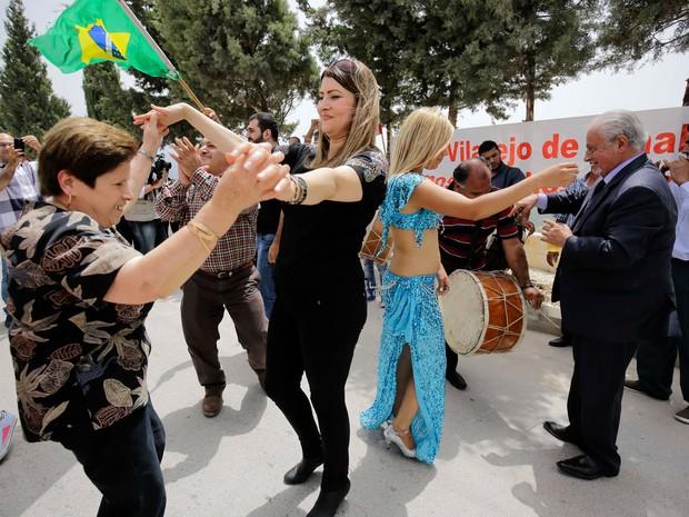 Pessoas com bandeiras do Brasil comemoram a posse de Michel Temer como presidente em exercício na aldeia libanesa de Btaaboura, ao norte de Beirute, no Líbano. Temer é filho de libaneses e visitou Btaaboura, onde seu pai cresceu, em 1997 e 2011 (Foto: Ibrahim Chalhoub/AFP)