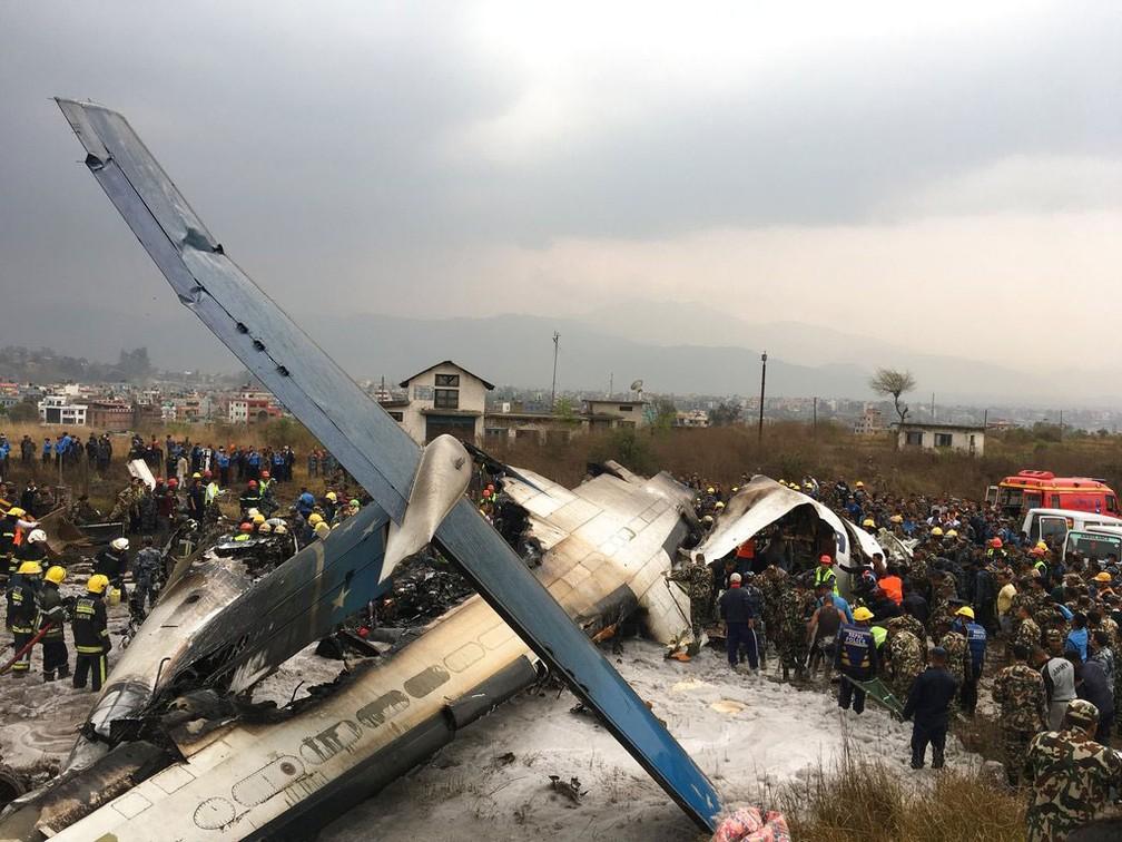 Equipes de resgate trabalham após avião cair no aeroporto de Katmandu, no Nepal, na manhã desta segunda-feira (12)  (Foto: Niranjan Shreshta/ AP)