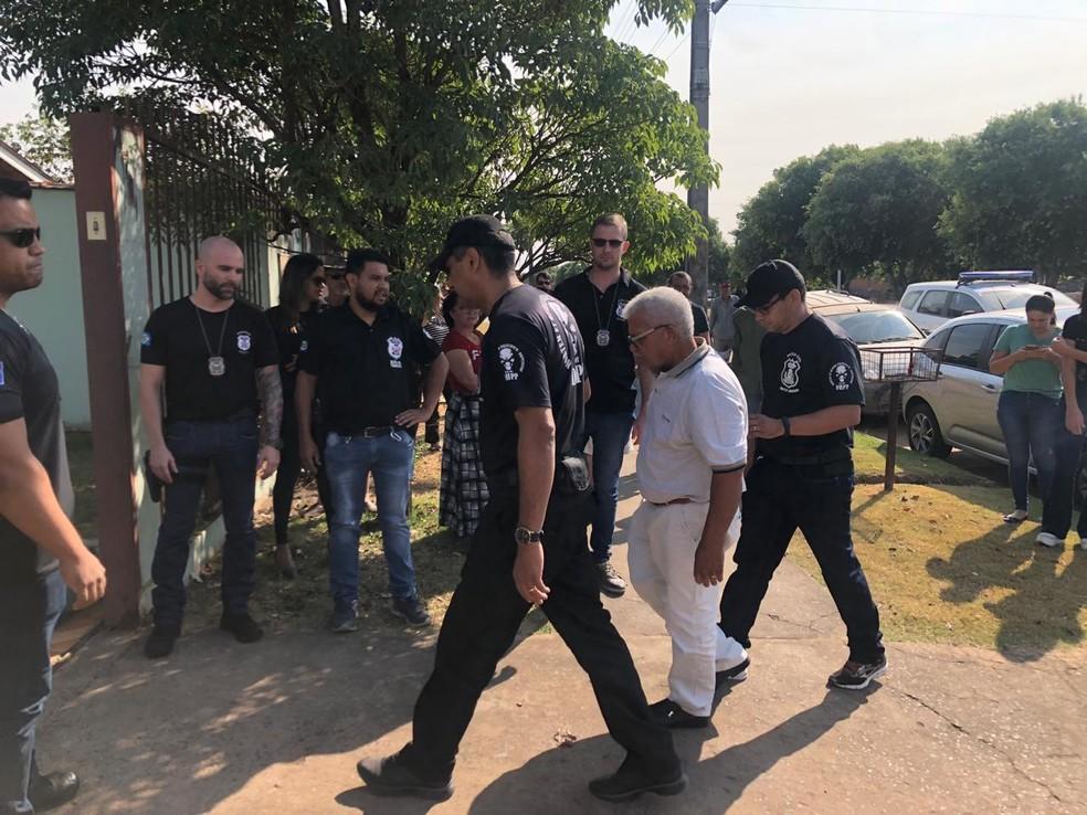 Jairo Narciso da Silva (de branco), de 64 anos, chegou escoltado por policiais para acompanhar a escavação dos restos mortais da mulher dele em Sinop — Foto: Poliana Mazzo/TV Centro América