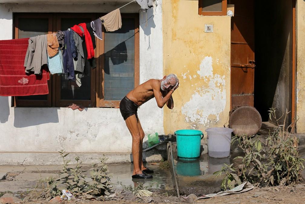 8 de janeiro - Um homem lava a cabeça enquanto toma banho em um mercado de Jammu, na Índia (Foto: Mukesh Gupta/Reuters)