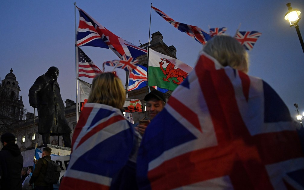 Apoiadores do Brexit agitam bandeiras do Reino Unido e do País de Gales perto da estátua de Winston Churchill, em Londres, no Dia do Brexit, na sexta-feira (31) — Foto: Daniel Leal-Olivas/AFP