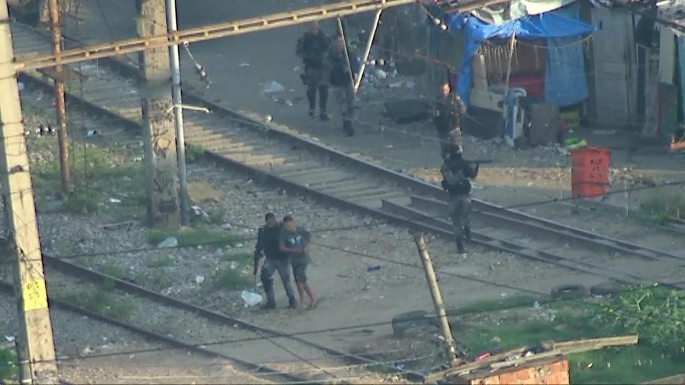 Suspeito é conduzido por policial na comunidade do Jacarezinho, no Rio — Foto: Reprodução/ TV Globo