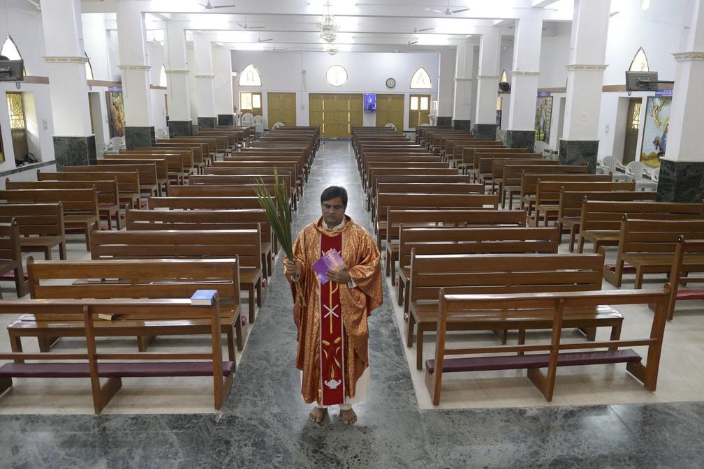 5 de abril - Padre celebra missa de Domingo de Ramos sozinho em igreja católica durante quarentena na Índia — Foto: Noah Seelam/AFP