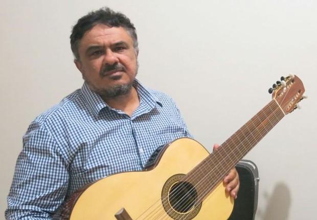 Reinaldo Casteluzzo com sua invenção: um violão de 12 cordas, que pode ser tocado com uma só mão (Foto: Arquivo pessoal via BBC)